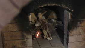 Mężczyzna rozognia ogienia w kuchence czerwona cegła zbiory wideo