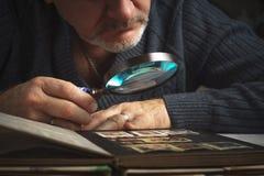Mężczyzna rozważa coś synklina powiększać - szkło Zdjęcie Stock