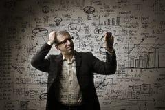 Mężczyzna rozwiązuje maths problemy Obrazy Stock