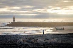 Mężczyzna, rybak i Łódkowaty pobliski bakan przy oceanem, obraz royalty free
