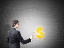 Mężczyzna rysunkowy żółty dolarowy znak na blackboard Zdjęcia Royalty Free