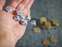 Mężczyzna rzuca gemowych kostka do gry na stole z monetami Pieniądze i gry sześciany Zdjęcie Royalty Free