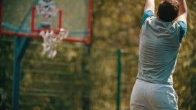 Mężczyzna rzuca piłkę w koszykówka obręczu i uderza cel - pokazywać «zadowalającego «gest zbiory