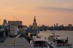 Mężczyzna są odpoczynkowi na nabrzeżu i kościół, Ukraina, Kyiv editorial 08 03 2017 Zdjęcia Stock