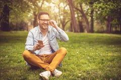 Mężczyzna słuchająca muzyka przy parkiem zdjęcia royalty free