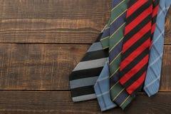 Mężczyzna ` s akcesoria Mężczyzna ` s styl różni krawaty na brązu drewnianym tle Mieszkanie nieatutowy Z przestrzenią dla teksta  zdjęcie royalty free