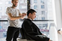 Mężczyzna ` s hairstyling i haircutting w fryzjera męskiego sklepie włosianym salonie lub fotografia stock