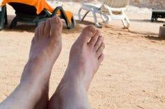 Mężczyzna ` s nagie nogi, cieki przeciw tłu słońc łóżka, deckchairs na plaży przeciw tłu tropikalny kurort Zdjęcia Stock