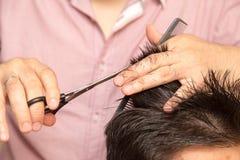 Mężczyzna ` s ostrzyżenie z nożycami przy salonem fotografia stock