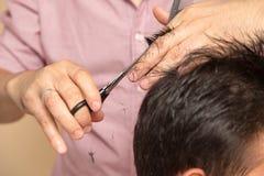 Mężczyzna ` s ostrzyżenie z nożycami przy salonem fotografia royalty free