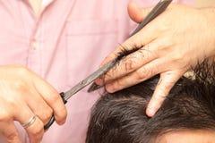 Mężczyzna ` s ostrzyżenie z nożycami przy salonem zdjęcie stock