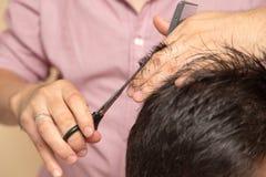 Mężczyzna ` s ostrzyżenie z nożycami przy salonem obraz stock