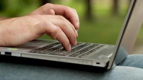 Mężczyzna ` s palce pisać na maszynie słowa na klawiaturze laptop Trzyma komputerowy na nogach Mężczyzna jest siedzącym outside w zbiory