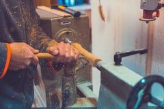 Mężczyzna ` s ręk chwyta ścinak blisko tokarki, mężczyzna pracuje przy małą drewnianą tokarką, rzemieślnik rzeźbi kawałek drewno  Obraz Stock