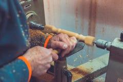 Mężczyzna ` s ręk chwyta ścinak blisko tokarki, mężczyzna pracuje przy małą drewnianą tokarką, rzemieślnik rzeźbi kawałek drewno  Obrazy Stock