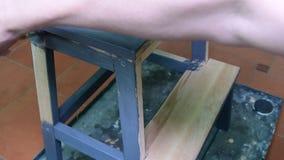 Mężczyzna ` s ręka maluje meblarską krok stolec Szary narzut Malować krok stolec z popielatym kolorem zbiory wideo