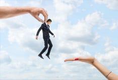 Mężczyzna ` s ręka niesie troszkę biznesmena kobiety ` s ręka na backgroung niebieskie niebo Obrazy Stock