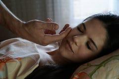 Mężczyzna ` s ręka pieści dziewczyny ` s twarz w ranku Dziewczyna jest uśmiechnięta dzień dobry przebudzenie obrazy royalty free