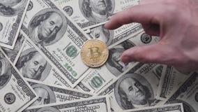 Mężczyzna ` s ręka stawia złocistą bitcoin monetę na my 100 dolarów Na całym świecie wirtualny interneta cryptocurrency i cyfrowa zdjęcie wideo