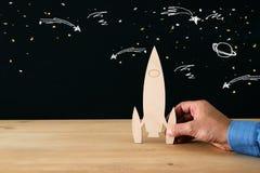 Mężczyzna ` s ręka trzyma drewnianą rakietę nad czarnym tłem z astronautycznym nakreśleniem, Obraz Stock