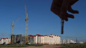 Mężczyzna ` s ręka trzyma klucze mieszkanie na tle budowa mieszkaniowy dom, zakończenie zdjęcie wideo