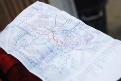 Mężczyzna ` s ręka trzyma mapę Podziemna metro lokalizować spotkanie Zamyka w górę mapy fotografia stock