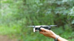 Mężczyzna ` s ręka trzyma quadrocopter lub trutnia przeciw tłu zieleni lasowe Przyszłościowe technologie zdjęcie wideo