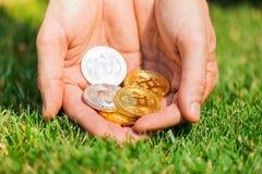 Mężczyzna ` s ręka trzyma złota i srebnej monety bitcoin Obrazy Royalty Free