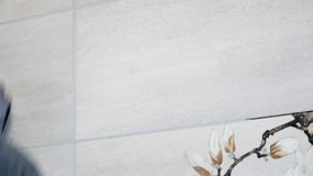 Mężczyzna ` s ręki kładzenia szwy beż płytki na ścianie z bliska zbiory