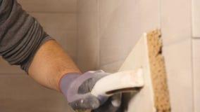 Mężczyzna ` s ręki kładzenia szwy beż płytki na ścianie z bliska zdjęcie wideo