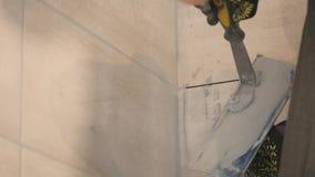 Mężczyzna ` s ręki kładzenia szwy beż płytki na ścianie z bliska swobodny ruch zbiory wideo