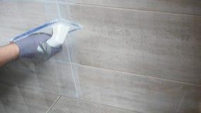 Mężczyzna ` s ręki kładzenia szwy beż płytki na ścianie z bliska swobodny ruch zdjęcie wideo