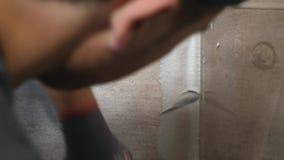 Mężczyzna ` s ręki kładzenia szwy beż płytki na ścianie z bliska swobodny ruch zbiory