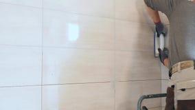 Mężczyzna ` s ręki kładzenia szwy beż płytki na ścianie Zamyka up, 4k zdjęcie wideo