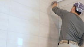 Mężczyzna ` s ręki kładzenia szwy beż płytki na ścianie Zamyka up, 4k zbiory wideo