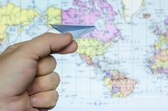 Mężczyzna ` s ręki mienia zabawki papierowy samolot przeciw mapie świat Zdjęcia Stock