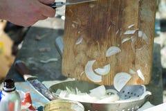 Mężczyzna ` s ręki pokrajać cebuli na drewnianej desce obrazy royalty free