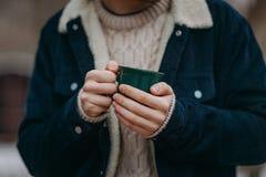 Mężczyzna ` s ręki trzyma zieloną filiżankę Obrazy Royalty Free