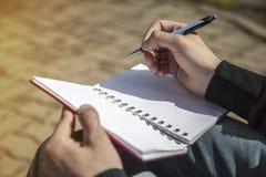 Mężczyzna ` s ręki writing na notatniku, sketchbook outdoors Zdjęcia Stock