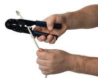 Mężczyzna ` s ręki z krajaczem cią kabel odizolowywającego na bielu obraz stock