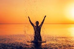 Mężczyzna ` s sylwetka w spokój wodzie przy zmierzchem Obraz Stock