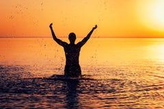 Mężczyzna ` s sylwetka w spokój wodzie przy zmierzchem Zdjęcie Stock