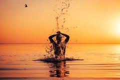 Mężczyzna ` s sylwetka w spokój wodzie przy zmierzchem Zdjęcia Stock