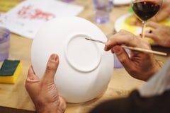Mężczyzna ` s wręcza malować ceramicznego talerza w sztuki studiu zdjęcie stock