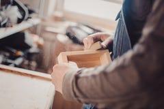 Mężczyzna sanding drewnianego panelu Proces ręczny sanding meblarska część Fotografia Stock