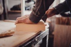 Mężczyzna sanding drewnianego panelu Proces ręczny sanding meblarska część Obraz Stock