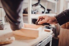 Mężczyzna sanding drewnianego panelu Proces ręczny sanding meblarska część Obrazy Stock