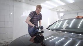 Mężczyzna sedulously poleruje zderzaka samochód zbiory