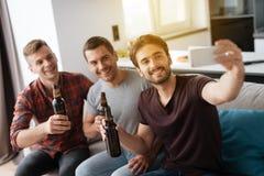 Mężczyzna siedzą na leżance i piją piwo Mężczyzna robi selfie z przyjaciółmi i piwem zdjęcia royalty free