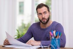 Mężczyzna siedzący główkowanie przy jego biurkiem Obraz Stock